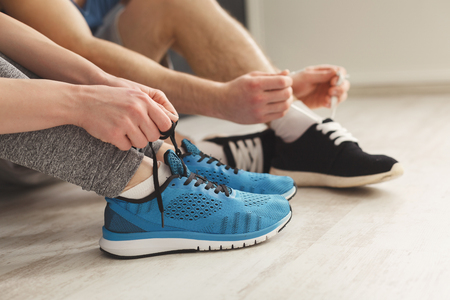 Couple tying up laces on sport shoes closeup. Unrecognizable man and woman preparing for training, wearing sneakers, copy space