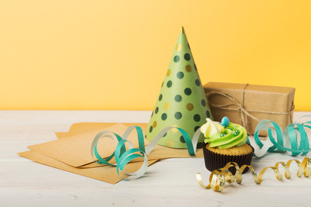Delicious cupcake, gift and dotted cap on yellow background, copy space. Birthday, party, holiday concept Imagens