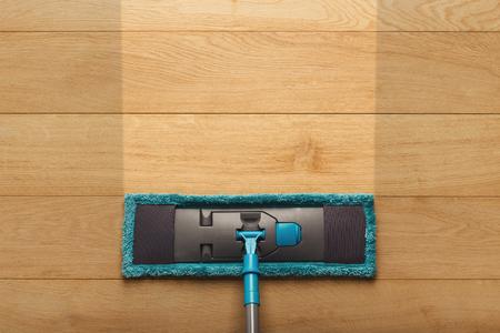 Antes y después del concepto de limpieza. Fregona azul sobre fondo de piso de parquet de madera. Servicios de limpieza, resultado y concepto de limpieza, espacio de copia Foto de archivo