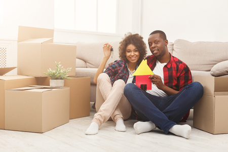Happy african-american family couple with house and key symbols. Sitting on floor against near storage boxes at new apartment. Moving and real estate concept, copy space, isolated Stockfoto - 97645476
