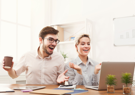 Smiling couple of young business partners working in modern office. Two coworkers discussing new project. Businesswoman smiling and pointing on tablet