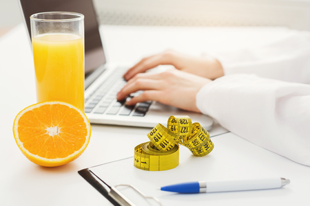 Female nutritionist working on laptop in office, close up. Hands of woman dietitian typing, counting calories or writing diet plan, copy space, selective focus