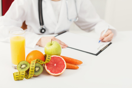 Nutritionist desk with healthy fruits, juice and measuring tape. Dietitian working on diet plan. Weight loss, healthy eating and right nutrition concept