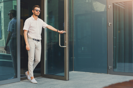 Confident pensive man opening the door and walking out from the modern office building, full length, copy space. Business, people and success concept Stockfoto