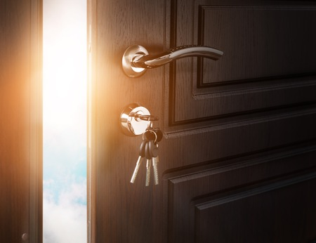 Half open door with keys in keyhole. Doorway to heaven and success. Entrance or exit, dreams and freedom conceptual background