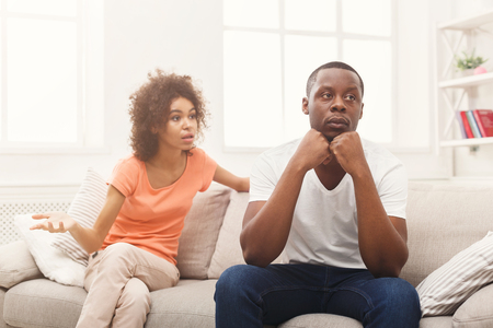 Young african-american couple quarreling at home, man offended. Family relationship difficulties concept, copy space 版權商用圖片