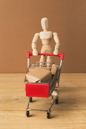Wooden mannequin with miniature toy shopping cart and parcels on brown background, business, shopping concept. Mockup for advertising of gifts, clothing, shopping, copy space.