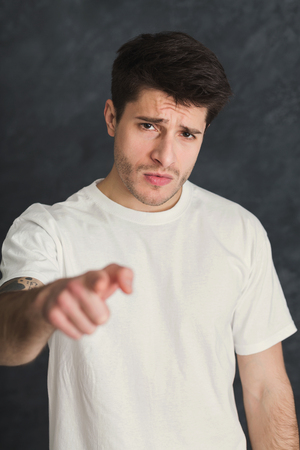 Strict serious young man point with index finger on camera, gray studio background. Motivation poster Stock Photo
