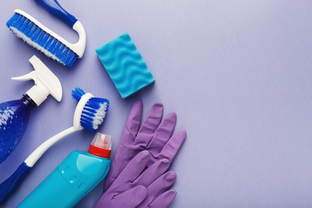 Spring cleaning background. Assortment of colorful spray detergents, sponges, rags and other supplies isolated on violet. Cleaning services and tidying up concept, top view, copy space Stock Photo