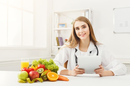 Female nutritionist working on digital tablet in office. Beautiful woman dietitian typing, counting calories or writing diet plan, copy space. Healthy eating concept Zdjęcie Seryjne