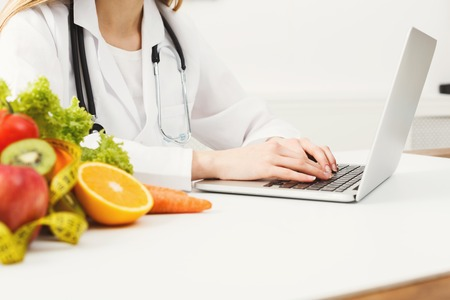 Female nutritionist working on laptop in office, close up. Hands of woman dietitian typing, counting calories or writing diet plan, copy space. Foto de archivo