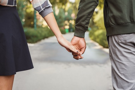 Multiethnic couple in love. Unrecognizable african-american man and asian woman walk in park, holding hands, closeup, copy space