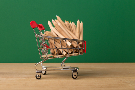 Miniature toy shopping cart with pencils on green background, business, shopping concept. Mockup for advertising of gifts, clothing, shopping, copy space.