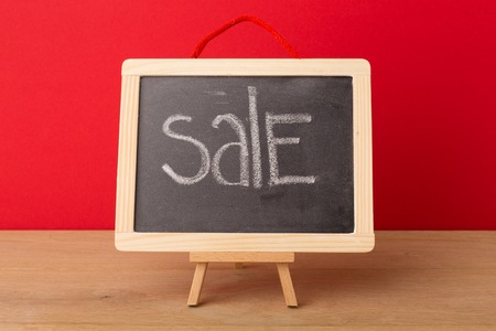 Sale word written on school blackboard against red background. Mockup for shopping, sales, black friday, copy space