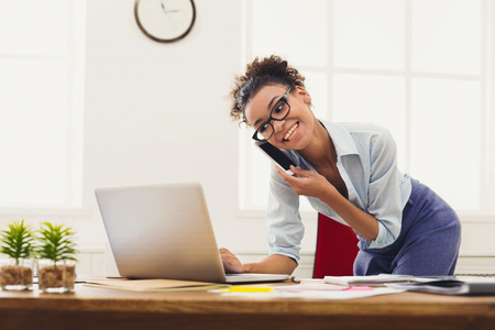 Glückliche AfroamerikanerGeschäftsfrau, die auf Mobile im Büro spricht. Der junge weibliche Manager, der am Telefon, unter Verwendung des Laptops am Arbeitsplatz sich berät, kopieren Raum Standard-Bild