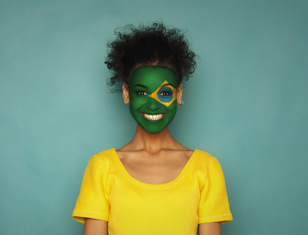Portrait of a woman with the flag of Brazil painted on her face. Football or soccer team fan, sport event, faceart and patriotism concept. Studio shot at blue background, copy space