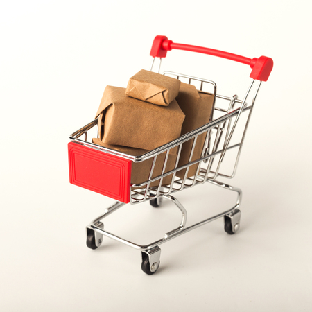 Miniature toy shopping cart and parcels isolated on white background, business, shopping concept. Mockup for advertising of gifts, clothing, shopping, copy space. Stock Photo
