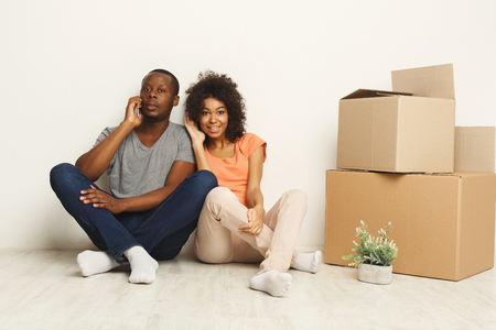 Happy african-american couple discussing design of new apartment, making order on mobile, sitting on floor at white wall near moving and storage boxes, copy space Foto de archivo