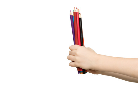 Childrens hand holding stack of colorful pencils, isolated on white background. Art, creativity, education concept Banque d'images