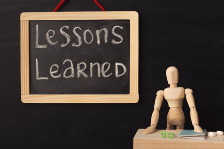 Wooden mannequin wrote word lessons learned on chalkboard in classroom over black background. Lessons, school, education concept.