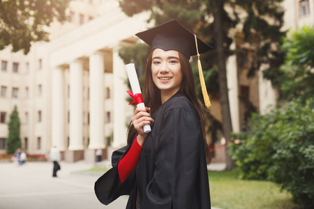 Young smiling woman on her graduation day in university holding diploma. Education, qualification and gown concept.