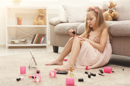 Curious little girl polishing her nails, sitting on the floor among lots of cosmetics at home. Princess in pink dress making herself beautiful Foto de archivo