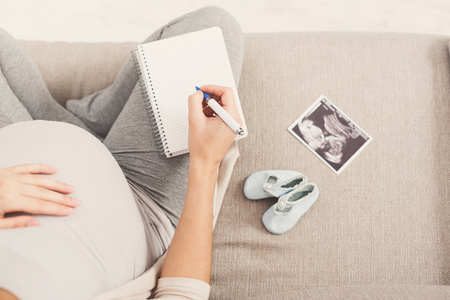 Unrecognizable pregnant woman sitting on sofa with blank notebook, pen, tiny shoes and sonogram and writing names for her baby, making shopping list, top view, copy space