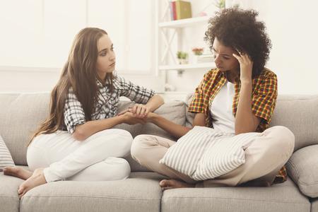 Zwei Frauen, die zu Hause über Probleme sprechen. Tröstende Freundschaft und Sorgfalt, unglückliches Mädchen stützen ihre Freundin, Kopienraum