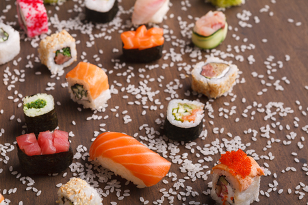 Japanese traditional cuisine. Close up of delicious set of various sushi, rolls and gunkans served on rustic wooden background with spilled rice, copy space Stock Photo