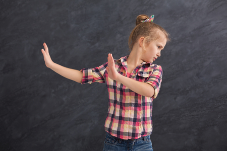 Little girl saying thanks but no. Cute child denying proposal, making stop gesture with her hands, copy space