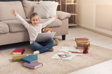 Happy little girl wins in computer game. Cute kid playing online on laptop, sitting on the floor at home with hands raised in the air, copy space