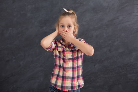 Little girl covering mouth and ear with hands while posing to camera on gray studio background, copy space Stock Photo