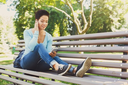 Handsome smiling girl sitting on a bench in the park listening to music on smartphone. Technology, communication, education and remote working concept, copy space