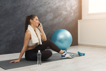 Happy fitness woman having rest and talking on smartphone after training. Young girl sitting on mat. Bodybuilding, healthy lifestyle concept, copy space Stock Photo