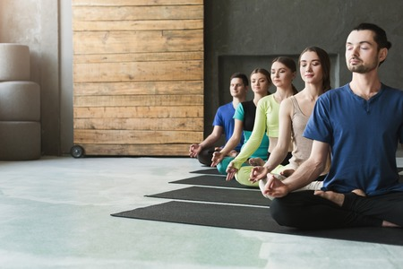 Young women and men in yoga class, meditation exercises. Lotus pose for relaxation. Healthy lifestyle in fitness club, crop, copy space