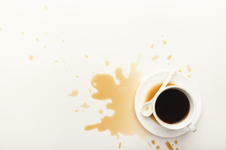 Cup of espresso and coffee spilt on white isolated background, top view. Mockup for grunge advertisement design, copy space