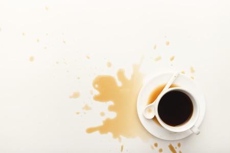 Schale Espresso und Kaffee, die auf Weiß verschüttet wurden, lokalisierte Hintergrund, Draufsicht. Modell für Schmutzanzeigenauslegung, Kopienraum Standard-Bild