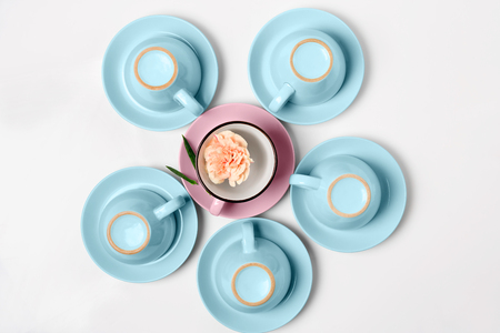 Overturned coffee or tea set. Plenty of elegant porcelain light blue and pastel pink cups bottoms and saucers at white isolated background, top view, flat lay Stock Photo