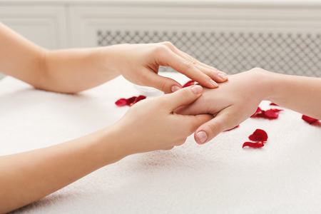 Hand massage at beauty salon. Manicure, nail and skin care at spa on white towel with rose petals, copy space Stock Photo