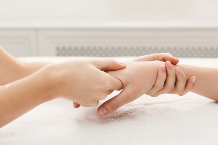 Hand massage at beauty salon. Manicure, nail and skin care at spa on white towel, copy space Stock Photo