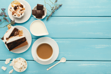 Morning coffee background. Border cappuccino cup, milk jar, chocolate, small cakes and refined sugar on blue rustic wooden table, copy space, top view Stock Photo