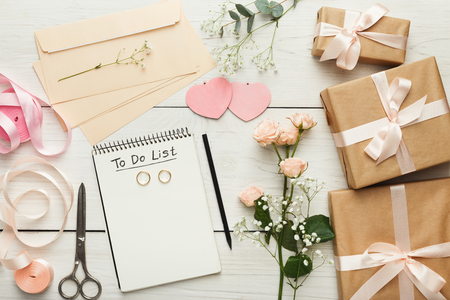 Wedding background with checklist. Paper planner and craft envelopes on white wooden table with lots of tender bridal stuff, top view 免版税图像