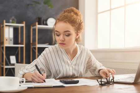 Financier woman in office working on laptop and writing financial accounts. Concentrated female manager working on marketing strategy at workplace