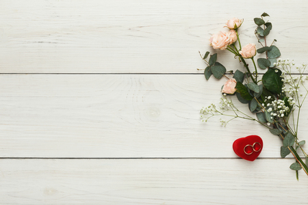 Golden wedding rings and pink roses on white rustic wood, top view. Marriage background with copy space