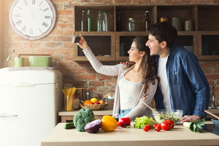 Happy couple cooking dinner and taking selfie in their loft kitchen at home. Preparing vegetable salad.