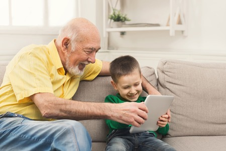 Cheerful senior man watching videos with grandson on digital tablet, sitting on couch at home, copy space