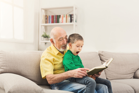 Senior man reading book for his grandchild. Cheerful grandfather telling fairy tale aloud to his excited grandson, sitting on couch at home, copy space