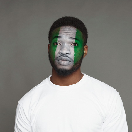 Face of young african-american unhappy man painted with flag of Nigeria. Football or soccer team fan, sport event, faceart and patriotism concept. Studio shot at gray background, copy space Stock Photo