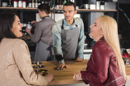 Smiling barista in uniform giving coffee cup to women. Small business, occupation people and service concept, copy space, selective focus Stock Photo