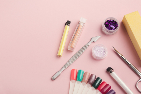 Manicure and pedicure beauty accessories on pink background, copy space. Nail polish samples, scissors, clippers and other supplies for home and salon procedure